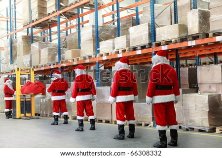 team of santa clauses standing in the line for the sacks of gifts in storehouse - stock photo