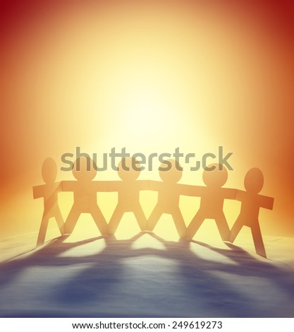 Team of six paper-chain people holding hands in front of bright sky