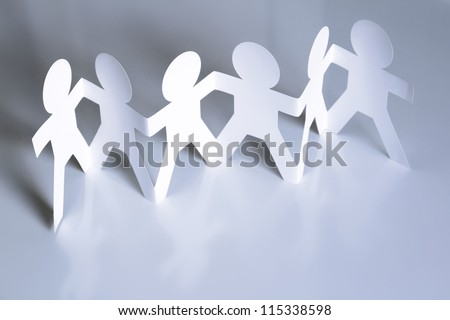 Team of six paper doll people holding hands. Teamwork concept - stock photo
