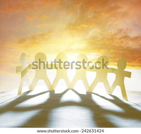 Team of six paperchain people holding hands in front of bright sky   - stock photo
