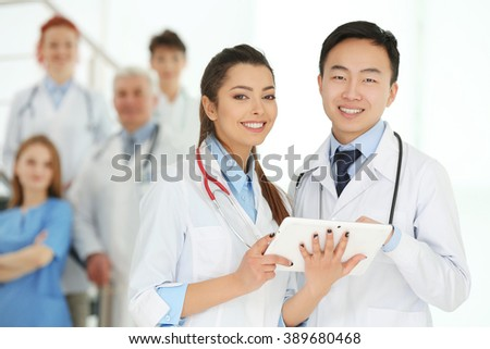 Team of smiling doctors indoors - stock photo