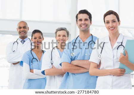 Team of smiling doctors looking at camera in medical office