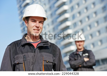 Team of smiling foreman builders workers in protective uniform at construction building site - stock photo