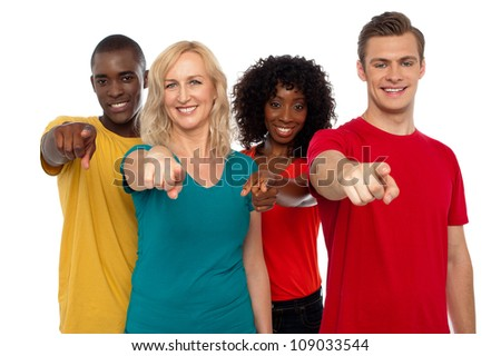Team of smiling teenagers indicating at you isolated over white background - stock photo