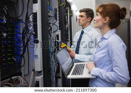 Team of technicians using digital cable analyser on servers in large data center - stock photo