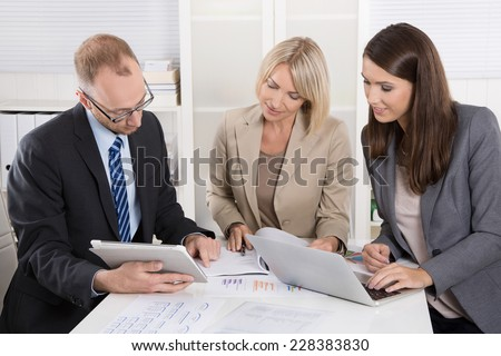 Team of three business people sitting together at desk in a meeting. Mature Couple Meeting Financial Advisor Home Stock Photo 550421866