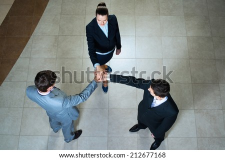 team of three businessmen clasped her hands together, a symbol of teamwork