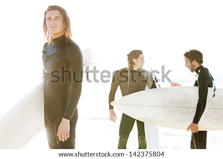 Team of three surfer men standing on a beach with their surfing boards after a surfing session, with the sunset and a golden glare light, while on vacation together. - stock photo