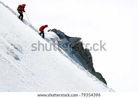 Team of two alpinists climbing a mountain - stock photo