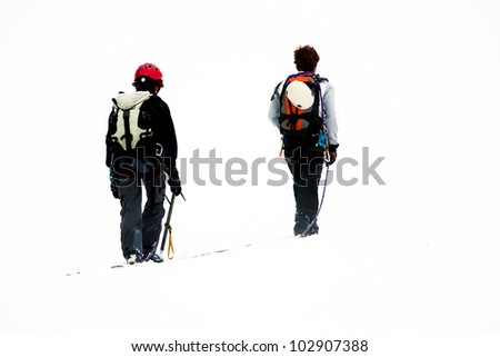 Team of two alpinists climbing a mountain during foggy weather - stock photo