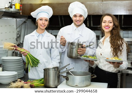 Team of two chefs and female waiter at restaurant kitchen. Selective focus