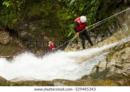 Team Of Two Young Women Wearing Waterproof Equipment Descending A Waterfall