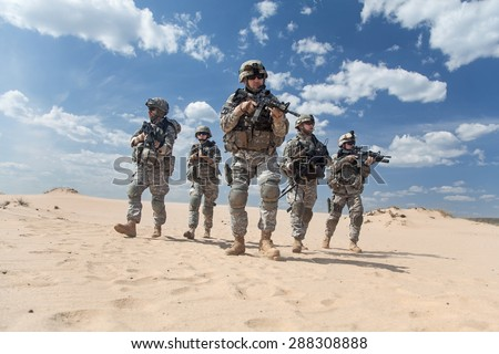 Team of United states airborne infantry men with weapons moving patrolling desert. Sand and blue sky on background of squad, sunlight, front view
