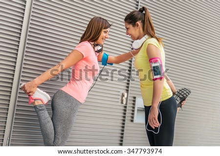 Team of urban runners getting ready for training - Sportive women with sportswear stretching before running  - Friends working out to keep fit and healthy - stock photo