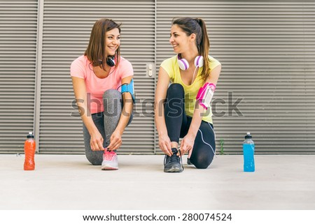 Team of urban runners getting ready for training - Sportive women with sportswear tying shoelaces  - Friends working out to keep fit and healthy - stock photo