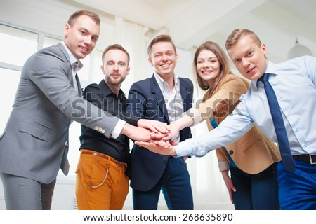 Team of winners. Partnership and creative work. Group of business people holding their hands together and smiling while standing on office. Focus on hands. - stock photo
