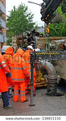 team of workers in rainwear works hard to install a pump road - stock photo