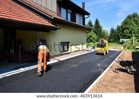 Team of Workers making and constructing asphalt road construction with steamroller. The top layer of asphalt road on a private residence house driveway - stock photo
