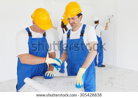 team of workmen looking at house design - stock photo
