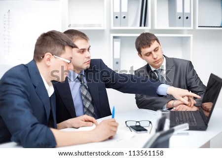 Team of young business men working at laptop together in a office