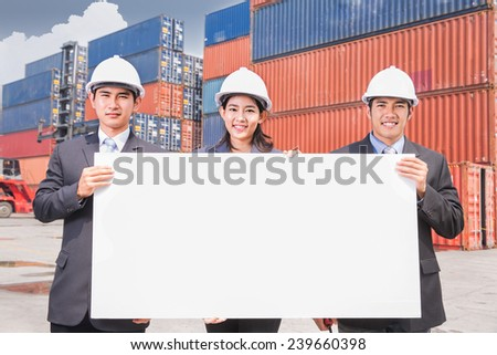 Team of young business people holding blank white board in logistic port - stock photo