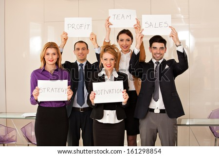 team of young business people holding cardboards: strategy, motivation, profit, team, sales