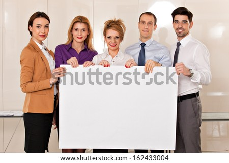 team of young business people, two men and three women,  holding a white cardboard - stock photo
