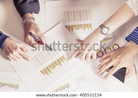 team of young businesspeople working together with hands on desk - stock photo