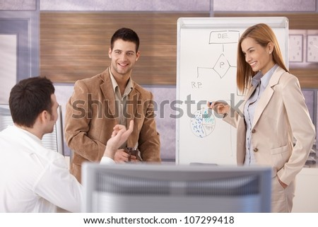 Team of young businesspeople working together, woman presenting, smiling. - stock photo