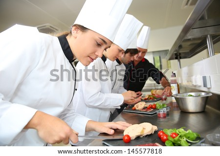 Team of young chefs preparing delicatessen dishes - stock photo