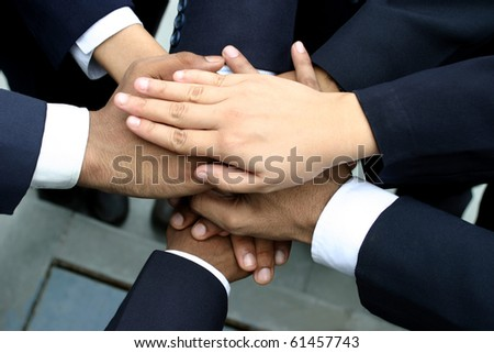 team of young executives keeping hands  together - stock photo