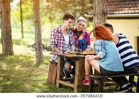 Team of young people with pleasure play chess on picnic