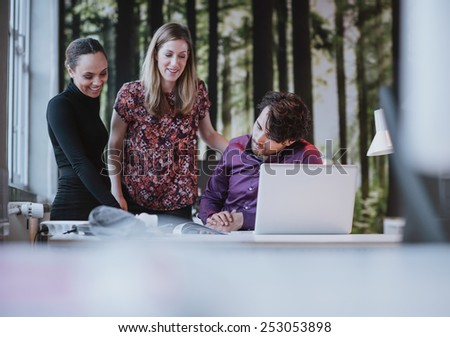 Team of young professionals looking at a catalogue and smiling. Creative team together viewing at a book on desk. - stock photo