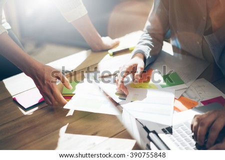 Team partnership. Photo young business managers  working with new startup project in office. Analyze document, plans. Generic design notebook on wood table, papers, documents. Horizontal, blurred - stock photo