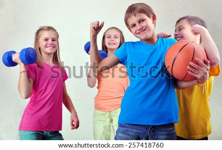 Team portrait of sportive kids friends with dumbbells and ball - stock photo
