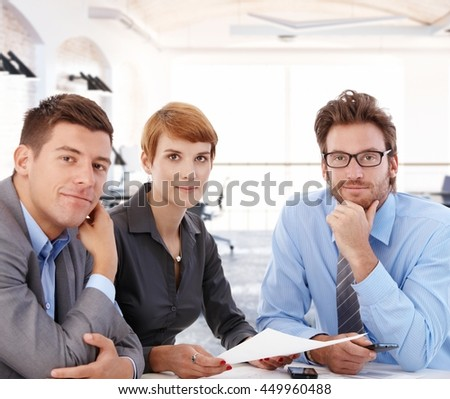 Team portrait of young businesspeople working together, sitting at desk, looking at camera. - stock photo