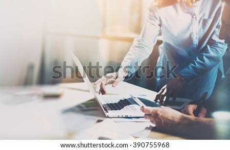 Team project. Photo young talent managers working with new startup project in modern office. Generic design notebook on wood table. Horizontal, sunset effect, blurred - stock photo
