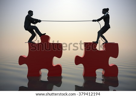 Team pulling jigsaw puzzle into position at sea since dawn. Two executives pull jigsaw puzzle pieces into position demonstrating teamwork at sea since dawn. - stock photo