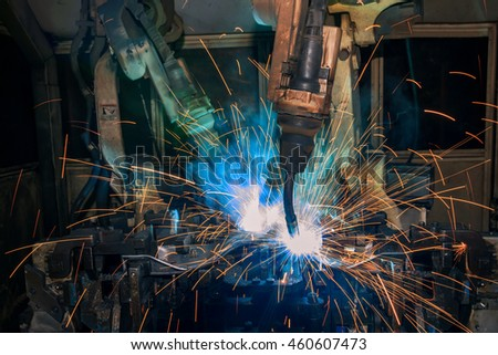 Team robot welding auto part in factory