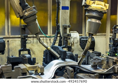 Team robots welding automotive parts in factory