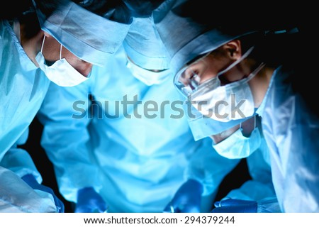 Team surgeon at work in operating room - stock photo
