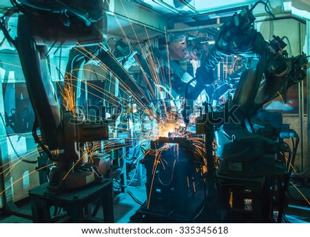 Team Welding robots movement in a car factory - stock photo