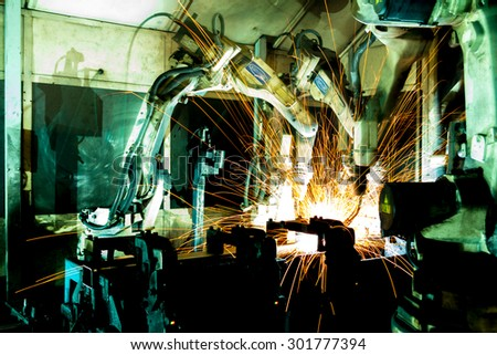 Team welding robots represent the movement. In the automotive parts industry. - stock photo