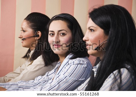 Team with three support operator women,focus on middle woman that looking at camera and smiling - stock photo