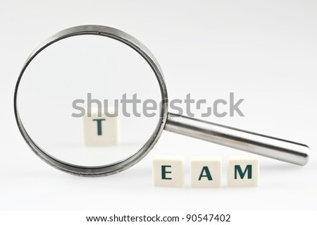 Team word and magnifying glass - stock photo