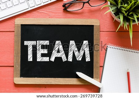 Team word Handwritten on blackboard. Team word Handwritten with chalk on blackboard, keyboard,notebook,glasses and green plant on wooden background - stock photo