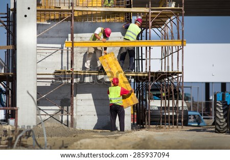 Team work at construction site, workers passing metal formworks on scaffolds - stock photo