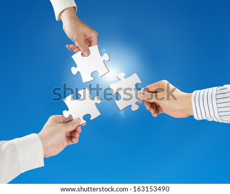 Team work concept, Hands hold puzzles with clear blue sky and sun light background  - stock photo