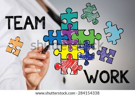 Team work concept. Young business woman drawing assembled puzzle that represent team support and help concept. - stock photo