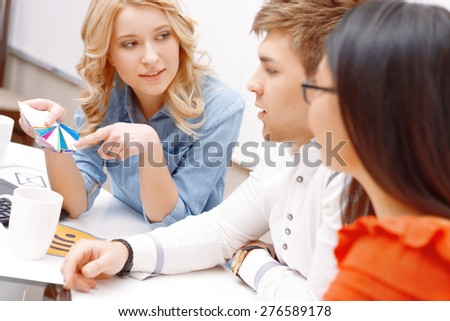 Team work. Team of young app developers choosing color from the palette while blond woman pointing at it in the light office - stock photo